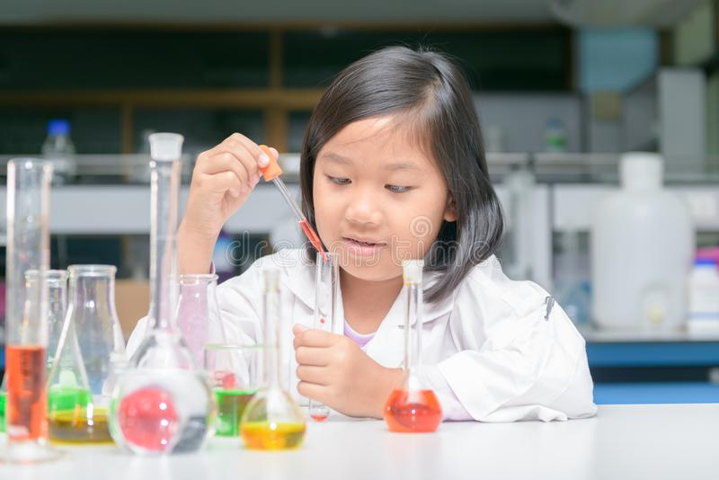 Happy little scientist in lab coat making experiment stock images