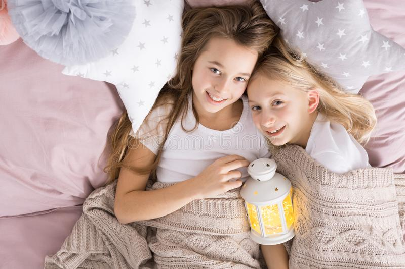 Happy little sister in bed royalty free stock photo