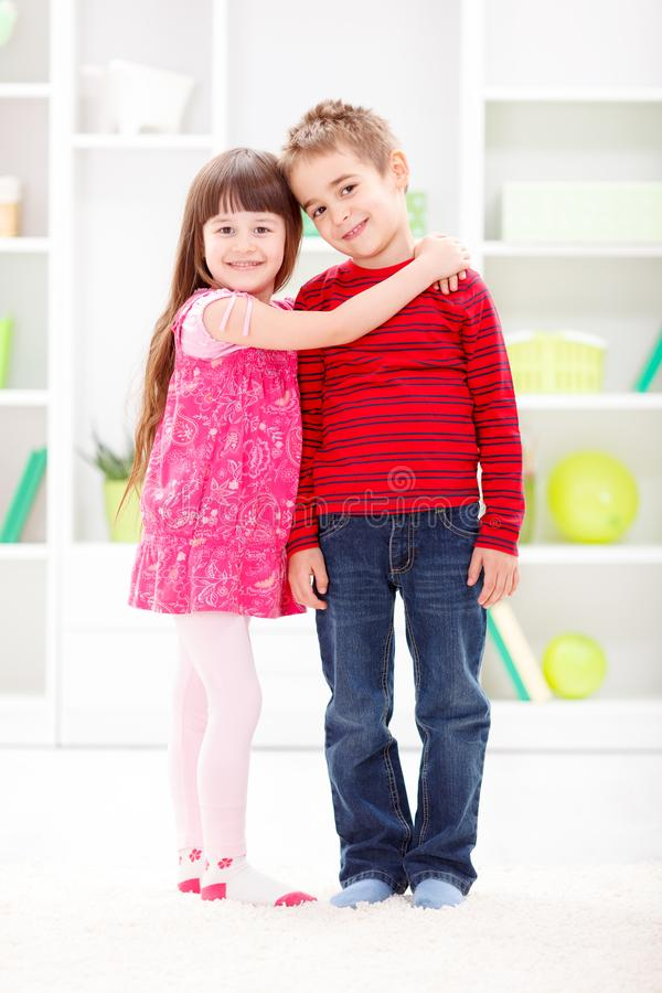 Little sister hugging her brother stock photos