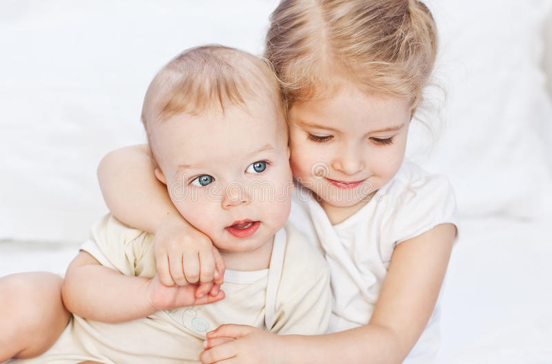 Happy little sister hugging her brother stock photos