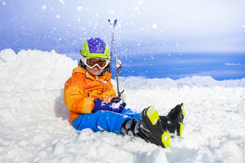 Happy little skier boy throw snow. Little boy with mountain ski clothes helmet and skies sit in snow and through snow up stock image