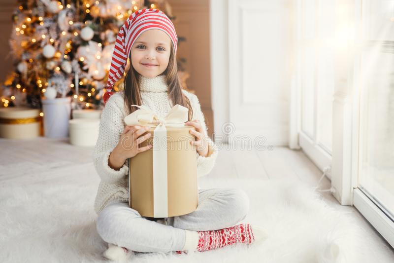 Happy little small child wears white knitted sweater holds gift sits in cozy room against New Year tree, feels comfort, glad to re royalty free stock photo