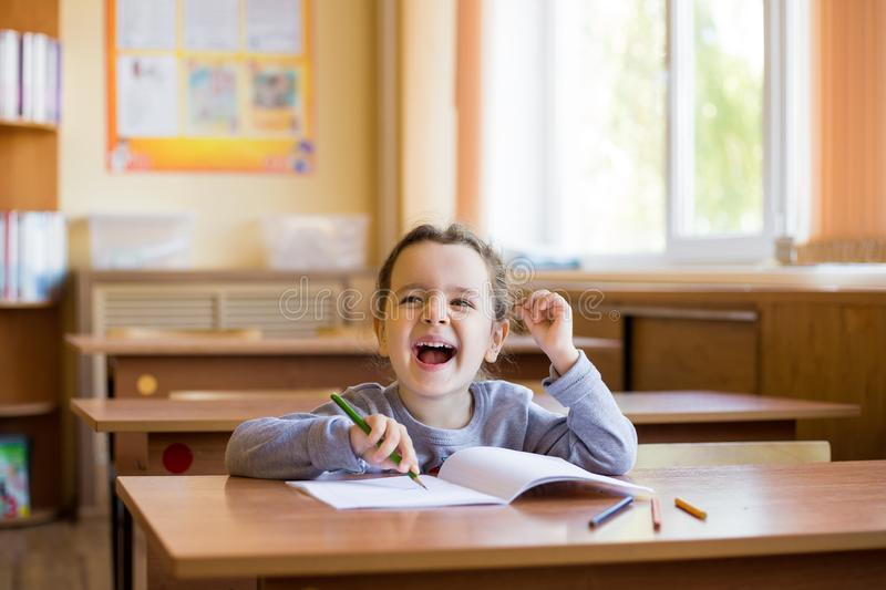 Happy little smiling girl sitting at desk in class room and begins to carefully draw in a pure notebook. Happy pupil.  stock image