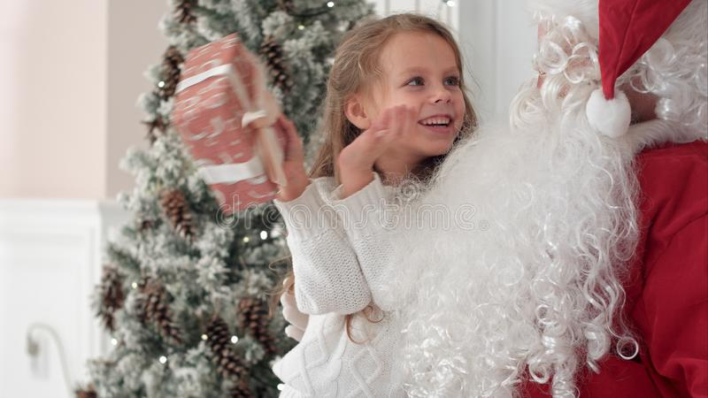 Happy little smiling girl trying to guess what is inside her christmas gift from Santa stock image