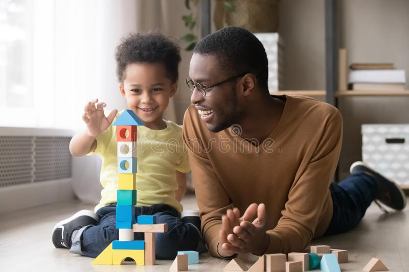 Happy little son playing with black dad using wooden blocks royalty free stock photos