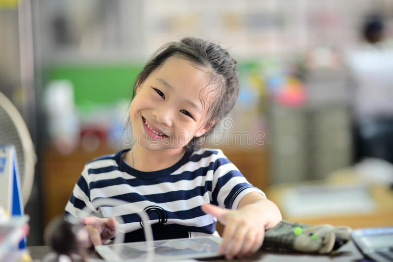 Happy little student Asian girl with tablet pc stock photo