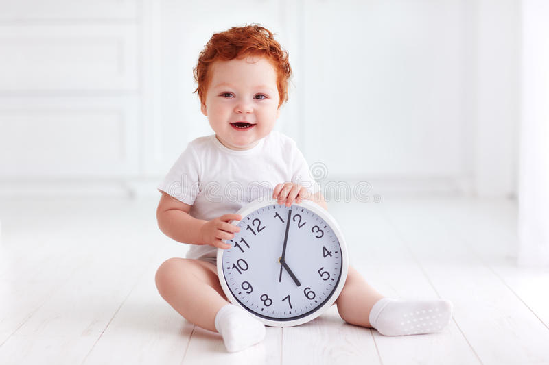 Happy little toddler baby holding circle clock stock photo