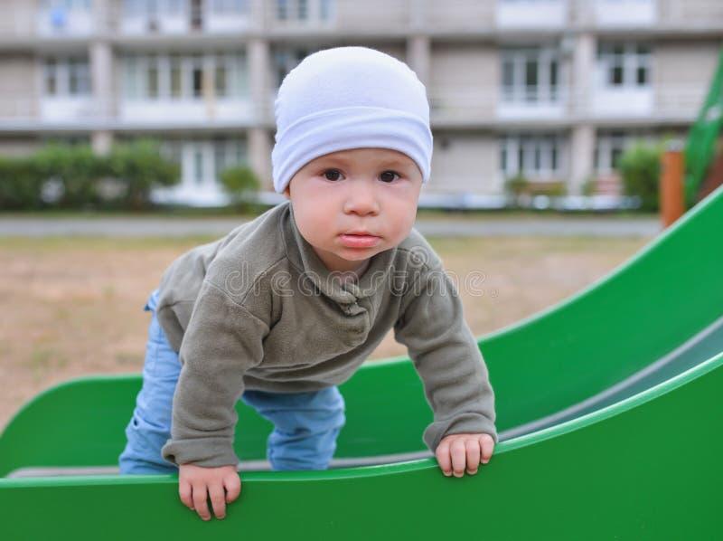 Happy little toddler boy having fun sliding on playground stock images