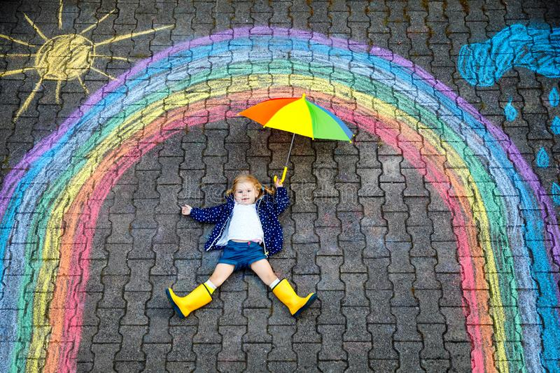 Happy little toddler girl in rubber boots with rainbow sun and clouds with rain painted with colorful chalks on ground. Or asphalt in summer. Cute child with royalty free stock photos