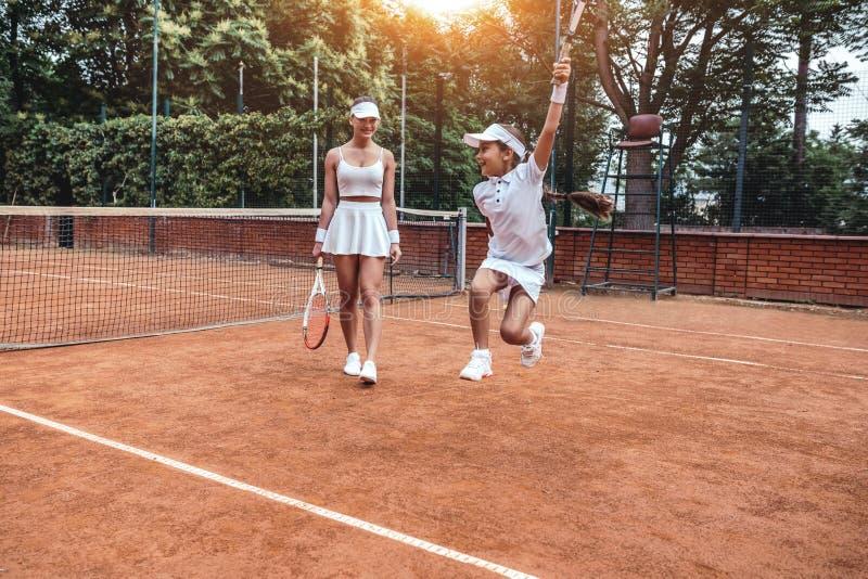 Happy little winner! Full length shot of two sporty girls in tennis club. Happy child having fun on tennis court with woman tennis. Happy little winner! Full stock photography