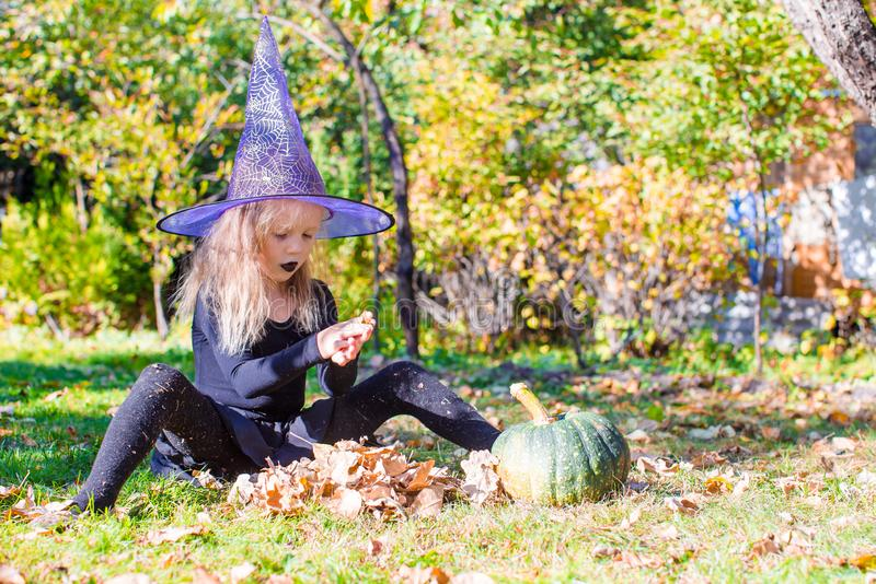 Happy little witch have fun outdoors on Halloween. Trick or treat. Happy girl in halloween costume with jack pumpkin.Trick or treat royalty free stock photo