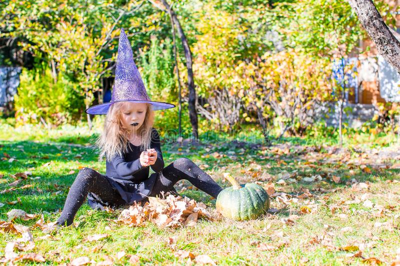 Happy little witch have fun outdoors on Halloween. Trick or treat. Happy girl in halloween costume with jack pumpkin.Trick or treat royalty free stock images