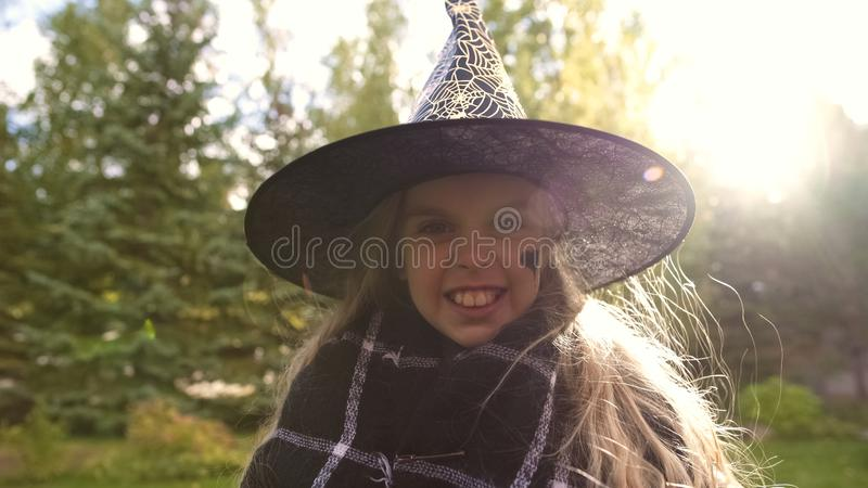 Happy little witch smiling at camera, children entertainment center, Halloween. Stock photo stock images