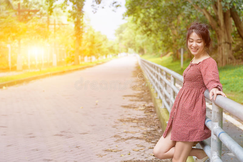 Happy long hair asian girl stand against fence with smile in sun. Ny day at summer time stock image
