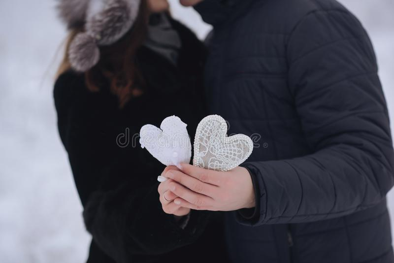 Happy love couple in the forest in winter, walk, kiss, hug and hold paper heart in park - Valentines Day. Happy love couple in the forest in winter, walk, kiss stock image