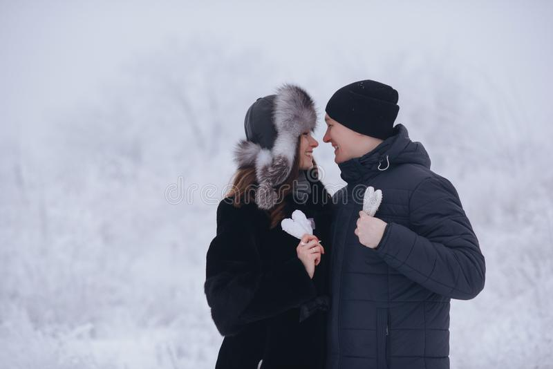 Happy love couple in the forest in winter, walk, kiss, hug and hold paper heart in park - Valentines Day. Happy love couple in the forest in winter, walk, kiss royalty free stock photo