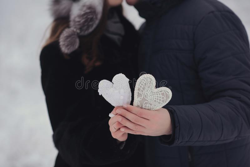 Happy love couple in the forest in winter, walk, kiss, hug and hold paper heart in park - Valentines Day. Happy love couple in the forest in winter, walk, kiss royalty free stock images