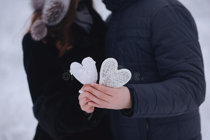 Happy love couple in the forest in winter, walk, kiss, hug and hold paper heart in park - Valentines Day. Happy love couple in the forest in winter, walk, kiss royalty free stock photography