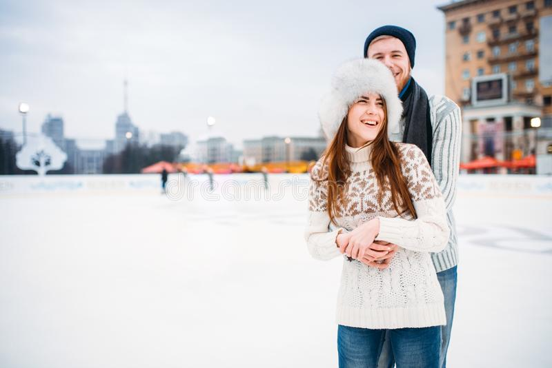 Happy love couple hugs on skating rink. Winter ice-skating on open air, active leisure, men and women skates together royalty free stock image