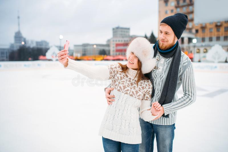 Happy love couple makes selfie on skating rink. Winter ice-skating on open air, active leisure, men and women skates together royalty free stock image
