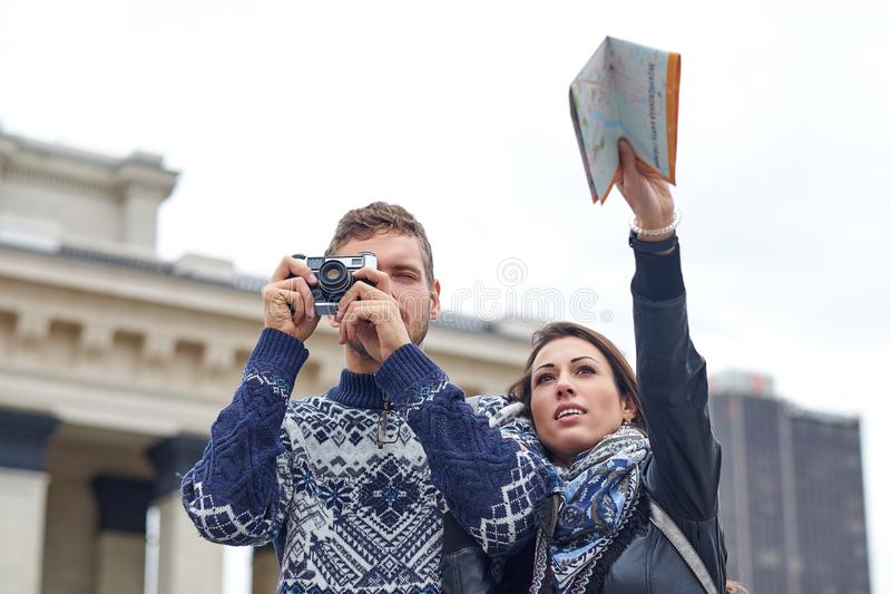 Happy love couple of tourists taking photo on excursion or city tour. Travel together with a map and retro camera royalty free stock photos