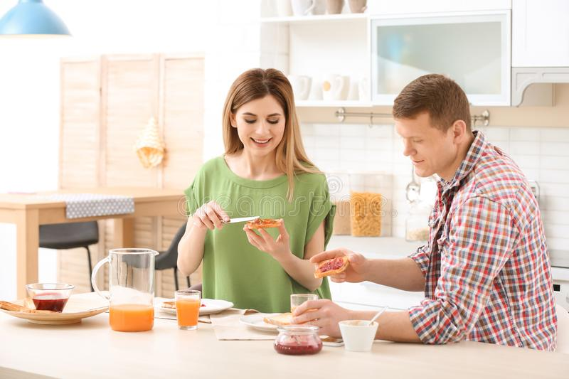 Happy lovely couple having breakfast with tasty bread at table in kitchen royalty free stock photo