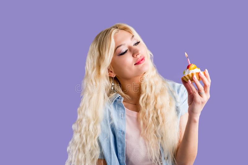 Happy lovely curly young woman holding birthday cupcake with candle. Happy cute lovely curly young blonde woman with makeup wearing casual clothes holding stock photography