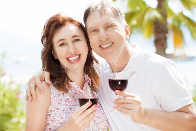 Happy lovely middle-aged man and woman hold glasses of red wine against the background of palm trees and the sea, summer concept royalty free stock images