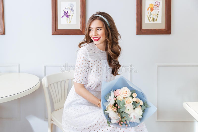 Happy lovely woman with bouquet of flowers sitting in cafe. Happy lovely young woman in white dress with bouquet of flowers sitting in cafe royalty free stock images