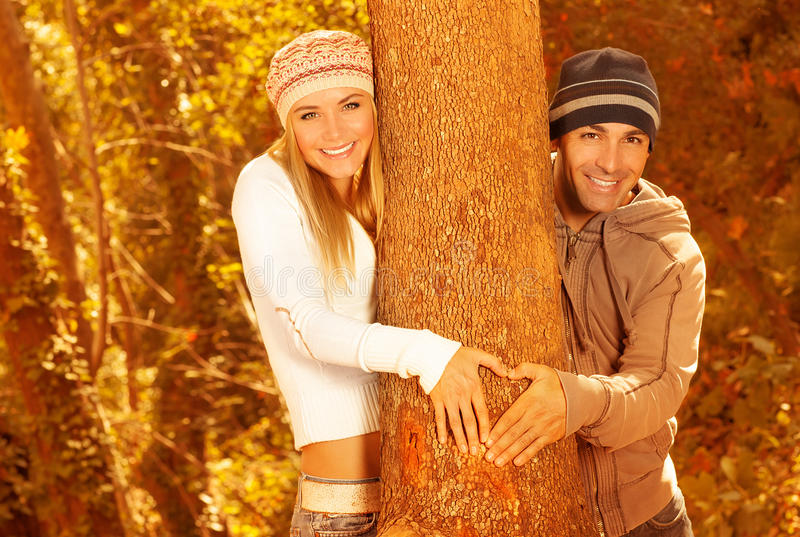 Happy lovers in autumn forest. Picture of two happy people having fun in autumnal forest, beautiful lovers hugging tree in fall park, boyfriend and girlfriend royalty free stock photography