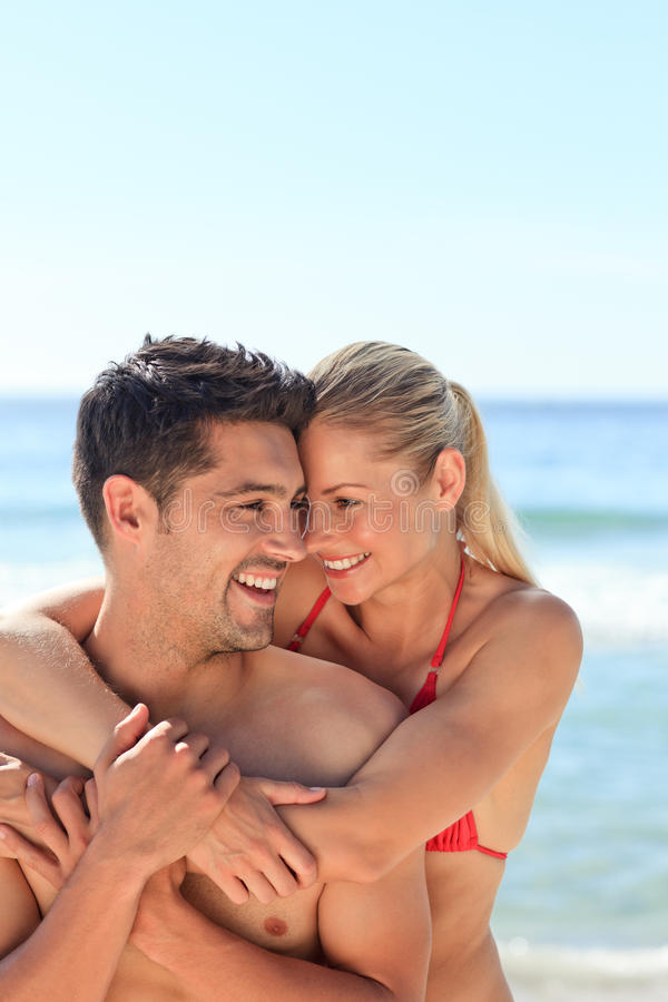 Happy lovers at the beach. Happy cute lovers at the beach stock image