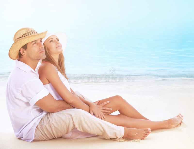Happy lovers on the beach. Beautiful young couple sitting on sandy coast and hugging, dreamy looking up in the sky and enjoying romantic honeymoon stock photography