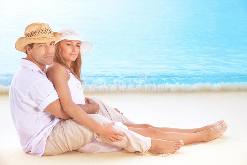 Happy lovers on the beach. Beautiful young couple sitting on sandy coast and hugging, enjoying each other and romantic honeymoon vacation royalty free stock photo