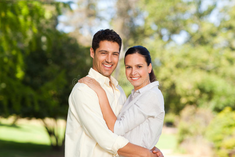 Happy lovers in the park. Young happy lovers in the park royalty free stock image