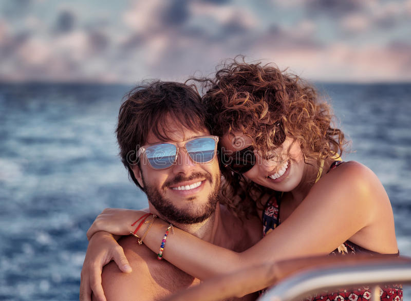 Happy lovers on sailboat. Closeup portrait of cheerful happy lovers on sailboat, young couple having fun in romantic sea traveling, love concept stock image