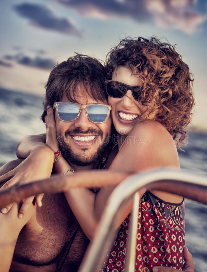 Happy lovers on sailboat. Closeup portrait of cheerful happy lovers on sailboat, young couple having fun in romantic sea traveling, love and enjoyment concept royalty free stock image