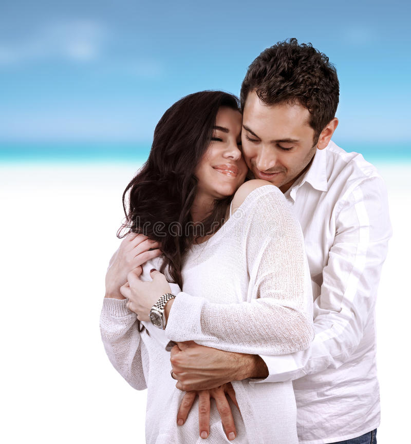 Happy lovers on vacation. Young arabic family hugging on the beach, spending time together, romantic relationship, love concept royalty free stock image