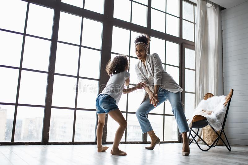 Happy loving afro american family. Young mother and her daughter playing in the nursery. Mom and daughter are dancing on the stock photography