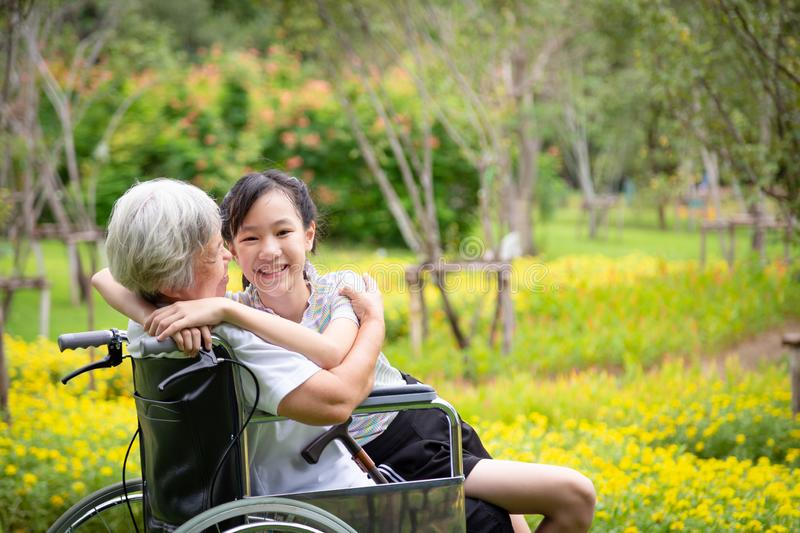Happy loving asian senior grandmother in wheelchair with beautiful child girl granddaughter embracing hugging and smiling together stock photography
