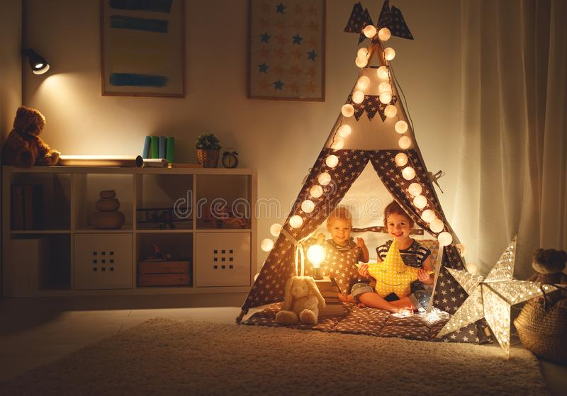 Happy loving children brother and sister play in dark tent in playroom at home stock images