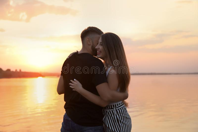Happy loving couple dancing near river at sunset stock photos