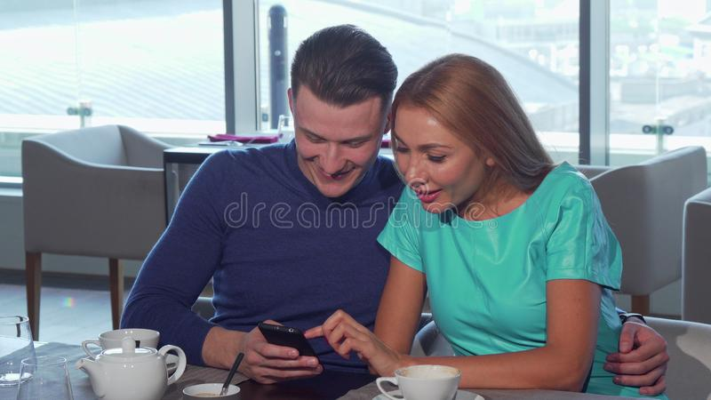 Happy loving couple embracing, using smart phone at the cafe together royalty free stock image