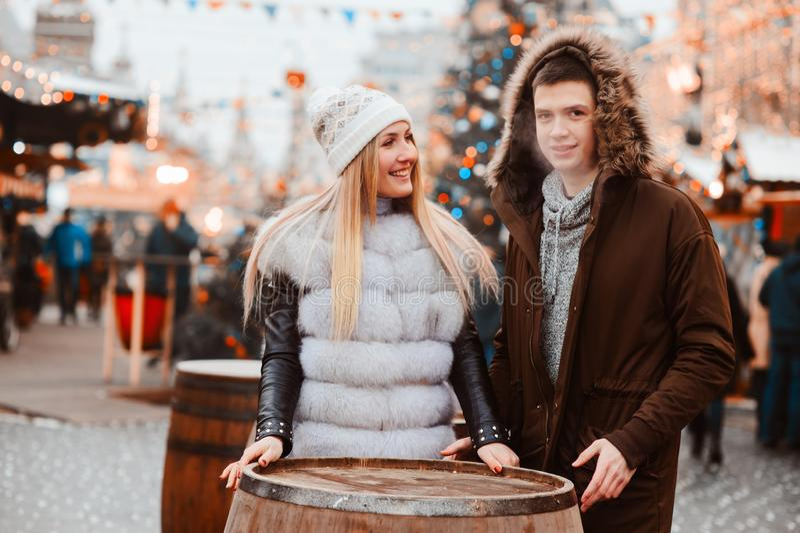 Happy loving couple enjoying Christmas or New year Holidays outdoor, walking on city festive market. With street food royalty free stock photos