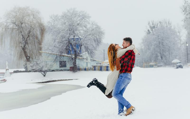 Happy loving couple is having fun in the winter forest. The man is spinning round his beautiful red head woman during. Happy loving couple is having fun in the royalty free stock photography