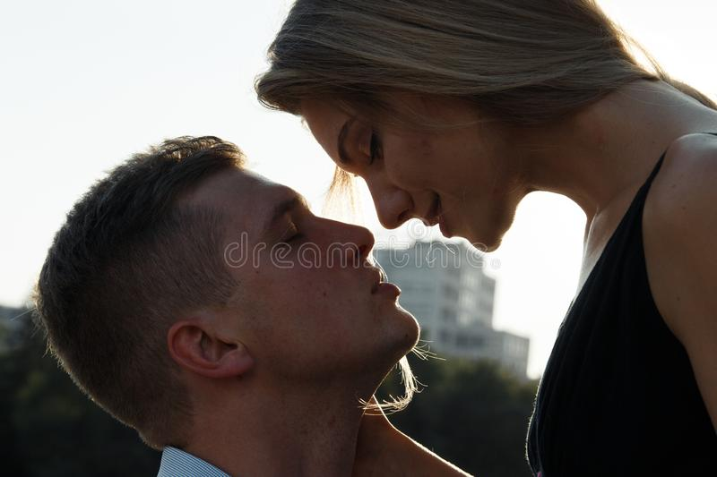 Happy loving couple hugging and kissing. dark background, the sun shines on lovers. sun rays in hair. The sun shines on lovers stock photos