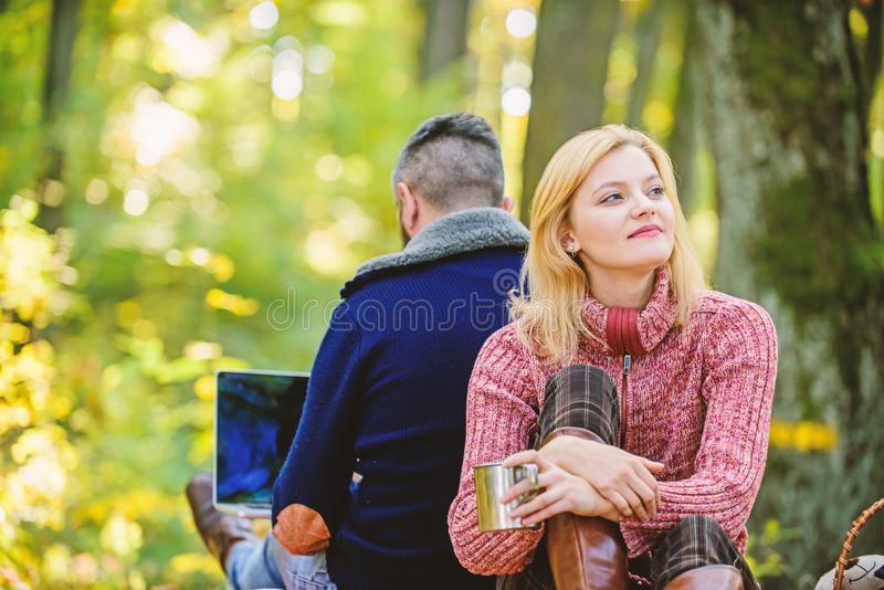 Happy loving couple relaxing in park with laptop. Always at work. Man freelance worker internet addicted gamer with. Laptop forest. Internet addicted husband stock images