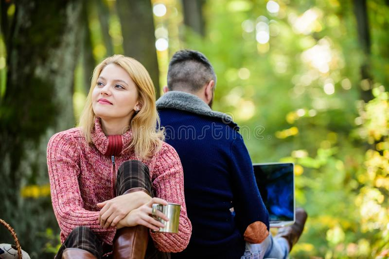 Happy loving couple relaxing in park with laptop. Always at work. Man freelance worker internet addicted gamer with stock photo