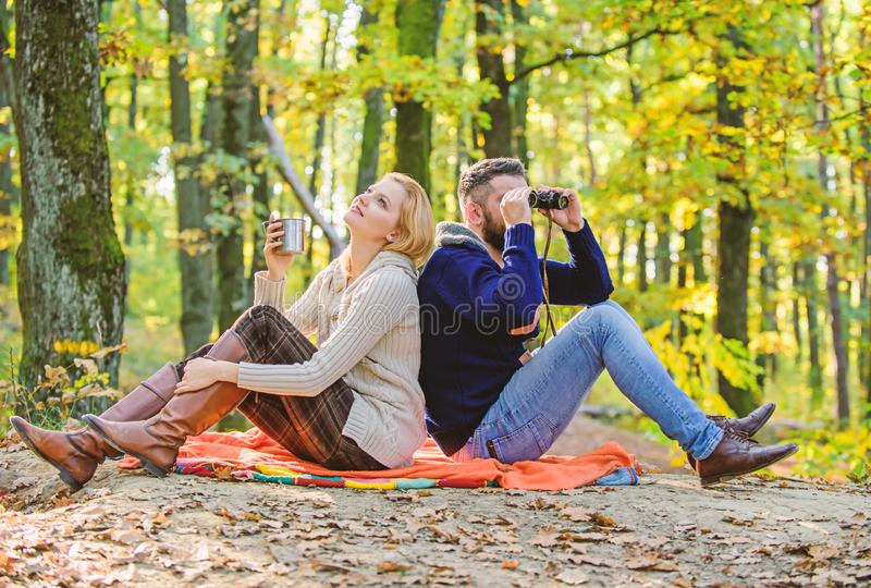 Happy loving couple relaxing in park together. Couple in love tourists relaxing picnic blanket. Man with binoculars and royalty free stock photos