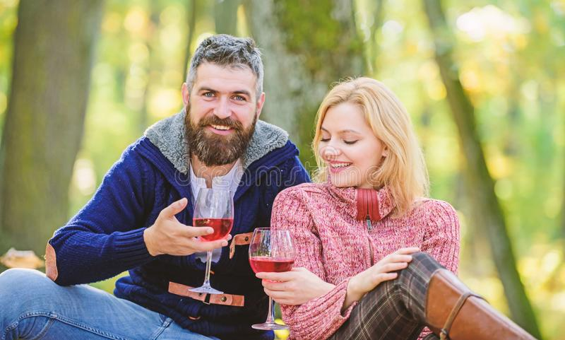 Happy loving couple relaxing in park together. Romantic picnic with wine in forest. Couple in love celebrate anniversary. Picnic date. Enjoying their perfect stock photo