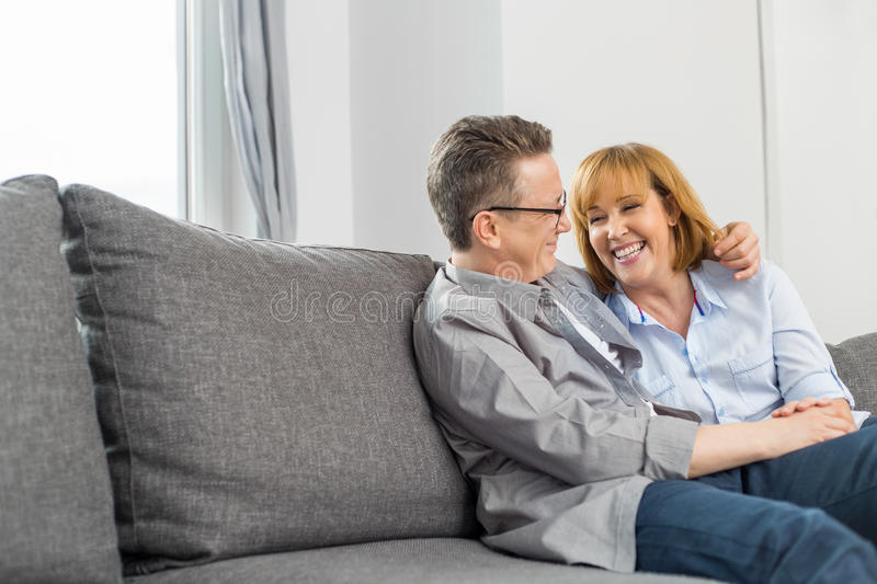 Happy loving couple sitting on sofa at home stock images